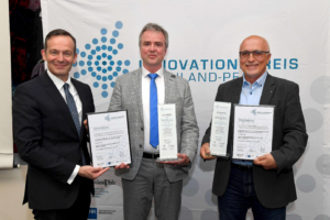 Oliver Hermanns, CEO of fleXstructures GmbH (middle), and Dr. Klaus Dreßler, Division Director Mathematics for Vehicle Engineering at Fraunhofer ITWM) (right) receive the award from Minister of Economics Dr. Volker Wissing (left). Foto: MWVLW-RLP/Kristina Schäfer